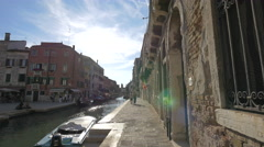 Two people walking on Fondamenta Alberti in Venice Stock Footage