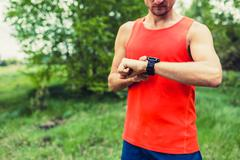 Runner looking at sport smart gps watch - stock photo