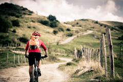 Mountain bike rider on country road, track trail in inspirational landscape Stock Photos