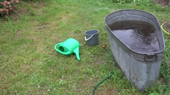 Tin water reservoir, watering can and water hose in rainy garden. 4K Stock Footage