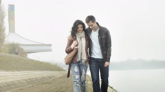 Romantic couple having a date, walking by the river, talking, smiling, hugging Stock Footage