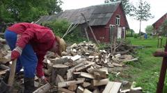 Poor gardener man chop wood near rural village house. 4K Stock Footage