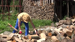 Tired gardener man drink water from plastic bottle and chop wood. 4K Stock Footage