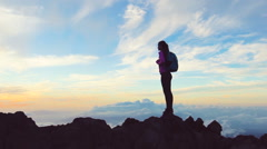 Lone female at sunset celebrates achieving her mountain hike above the clouds Stock Footage