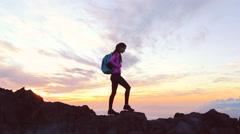Hiker walks along narrow summit ridge crest at sunset. Reaching the Top. Stock Footage
