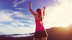 Reaching The Top. Happy successful fitness woman raising arms to the sky at s Stock Footage