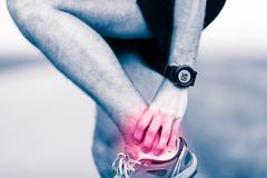 Leg ankle pain, man holding sore and painful foot Stock Photos