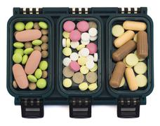 Multi-colored pills in green box organizer isolated on white Stock Photos