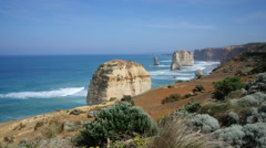 Australia Great Ocean Road 12 Apostles vista of sea stacks beyond shrubs Stock Footage