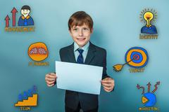 Teen boy businessman is smiling and holding a blank sheet of pap - stock photo