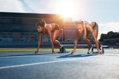 Determined female athletes ready to start a race - stock photo