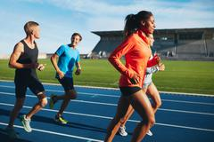 Fit men and women running on a race track Stock Photos
