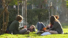 Teen age young people rest relax on a park grass smoking cigarettes - stock footage
