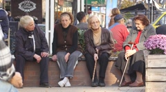 Stock Video Footage of Old age senior women sitting on a bench speaking in a city center street