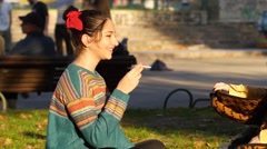 Teen age girl smoking cigarette sitting on a grass in a park Stock Footage