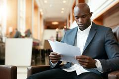 Young african businessman at hotel lobby reading documents - stock photo