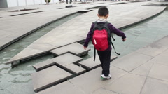 Young boy playing at a fountain in a park in Tokyo, Japan Stock Footage