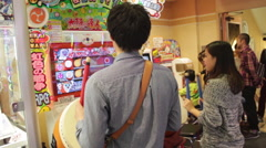 Young man and woman playing a drum video game in Shinjuku, Tokyo, Japan. Stock Footage