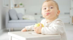 Cute 15-month-old baby girl eating an apple Stock Footage