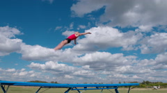 Athlete jumps on trampoline on background of clouds 4K Stock Footage