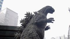 Pan down from buildings to a Godzilla statue in Tokyo, Japan Stock Footage