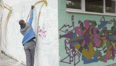 Two guys with spray paints graffiti on wall,pan left,other two graffiti artists. - stock footage