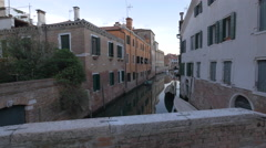Narrow canal with with buildings with window shutters in Venice - stock footage