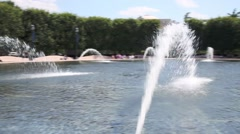 Beautiful fountain with fresh water in green park at sunny day Stock Footage