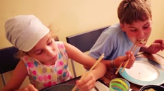 Boy and girl eat using of Chinese chopsticks  at home Stock Footage
