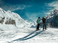 Skiers couple looking on the winter mountains in sun day. - stock photo