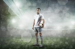 Stock Photo of Soccer player with ball in action at stadium under rain.