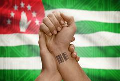 Barcode ID number tattoo on wrist of dark skinned person and national flag on - stock photo