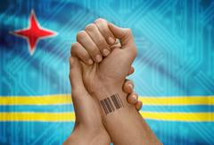 Barcode ID number tattoo on wrist of dark skinned person and national flag on Stock Photos