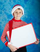 Smiling child in red Santa hat holding white board - stock photo