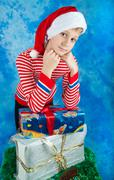Boy in Santa hat staying near christmas gifts - stock photo