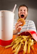 Expressive man eating fast food - stock photo