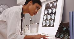 Young female medical assistant looking at x-ray scans Stock Photos