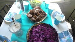 Baby shower party table, with blueberry pie, different cakes and blue baby cu Stock Footage