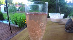 A glass filled with a pink sparkling wine drink, at a terrace table, in a gar Stock Footage