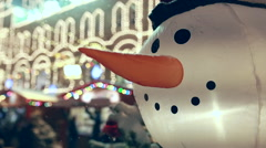 Funny Inflated Snowman Head with blurred lights at background - stock footage