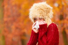 Sick woman in autumn park sneezing into tissue. Stock Photos