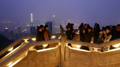 Tourists on Victoria Peak, against amazing night aerial skyline of Hong Kong Stock Footage