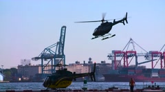Helicopter Flies Over Stationary Helicopter on New York Dock- Slow Motion - stock footage