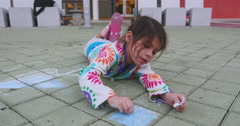 Child lying on floor drawing with chalk Stock Footage