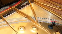 Inside of a piano with little hammer and strings Stock Photos