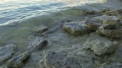 Small waves hitting rock shore Stock Footage