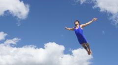 Athlete jumps on trampoline on background of clouds Stock Footage