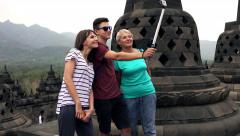 Family taking photo with camera on selfie stick in Borobudur temple in Indonesia Stock Footage
