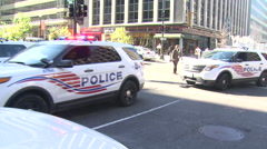 Police cars with Flashing lights going through intersection Stock Footage