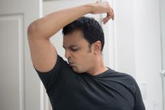 Closeup portrait, grumpy sweaty young man in black t-shirt, sniffing himself, - stock photo